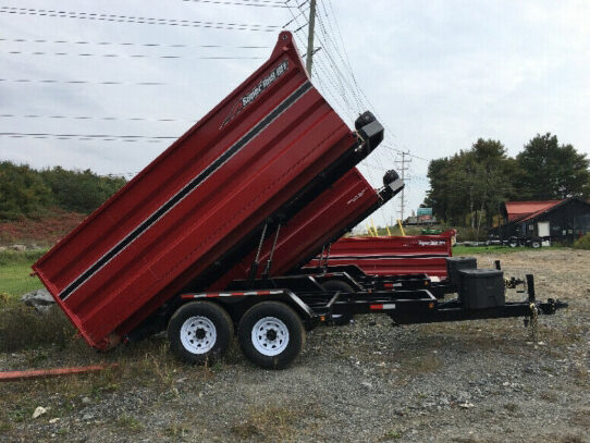 Photo of a dump trailer that is used by Hill's Junk Removal. Large dump trailer that is red.